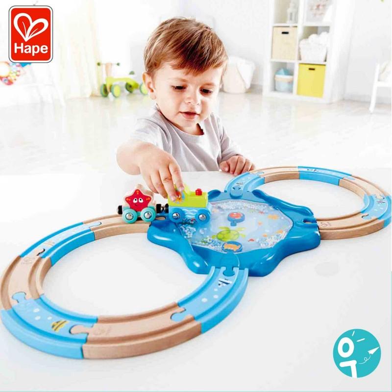 Petit garçon en train de jouer au circuit de train en bois sous marin Hape