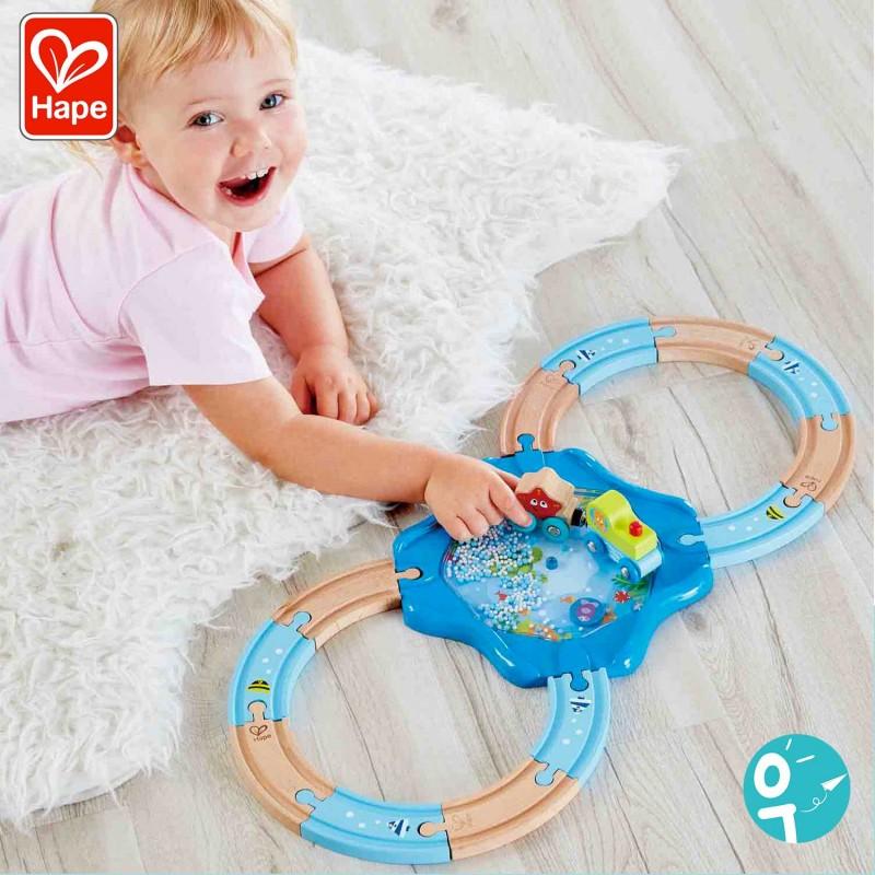 Petite fille en train de jouer au circuit de train en bois sous marin Hape