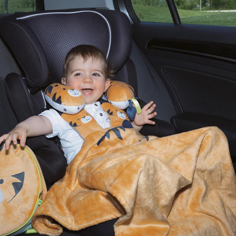 Enfant avec le coussin cale-tête dans voiture.
