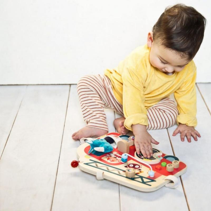 Bébé qui joue avec le panneau d'activités en bois camion de pompier de Lilliputiens.