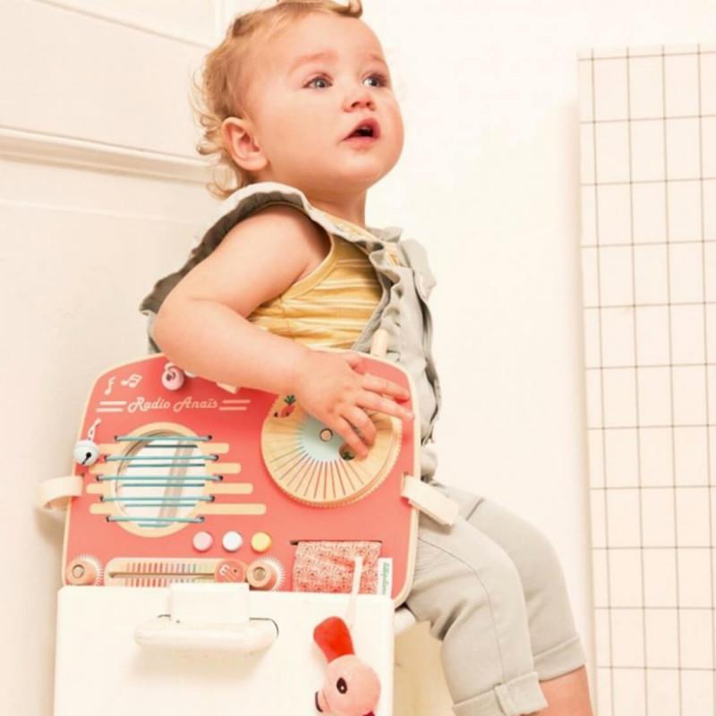 Bébé qui joue avec le panneau d'activités en bois radio d'Anaïs de Lilliputiens.